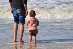 Father with young daughter at a beach on her day to be with dad