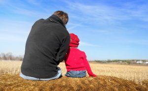 father & son sitting in wheat field