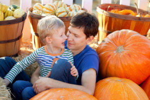 happy young father and his cute son spending fun time together at pumpkin patch; family of two at fall