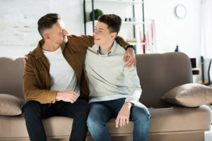 teenager and his dad sitting on a couch