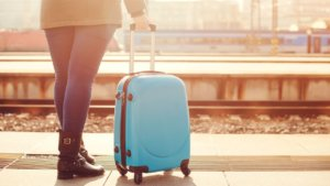 I Don't Know Where My Spouse Lives - Woman standing with rolling suitcase
